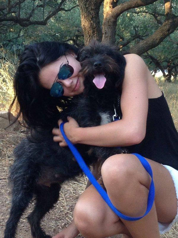Georgia Bradley with her stray dog Pepper. See SWNS story SWDOG: A British tourist being attacked by two men in Greece was saved by a stray DOG - and then spent thousands of pounds to bring the heroic pooch home to live with her. Holidaymaker Georgia Bradley, 25, was surrounded by the aggressive males when she rejected their advances on a remote beach. Student Georgia's boyfriend was in a nearby cafe when the two men approached her and asked her to go for a drink. She refused and one of the men grabbed her arm - but a small black abandoned dog suddenly ran over and started barking at them.