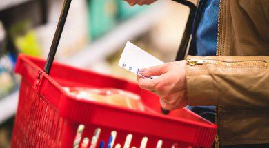 Hand Holding Shopping List And Basket In Grocery Store Aisle. Wo